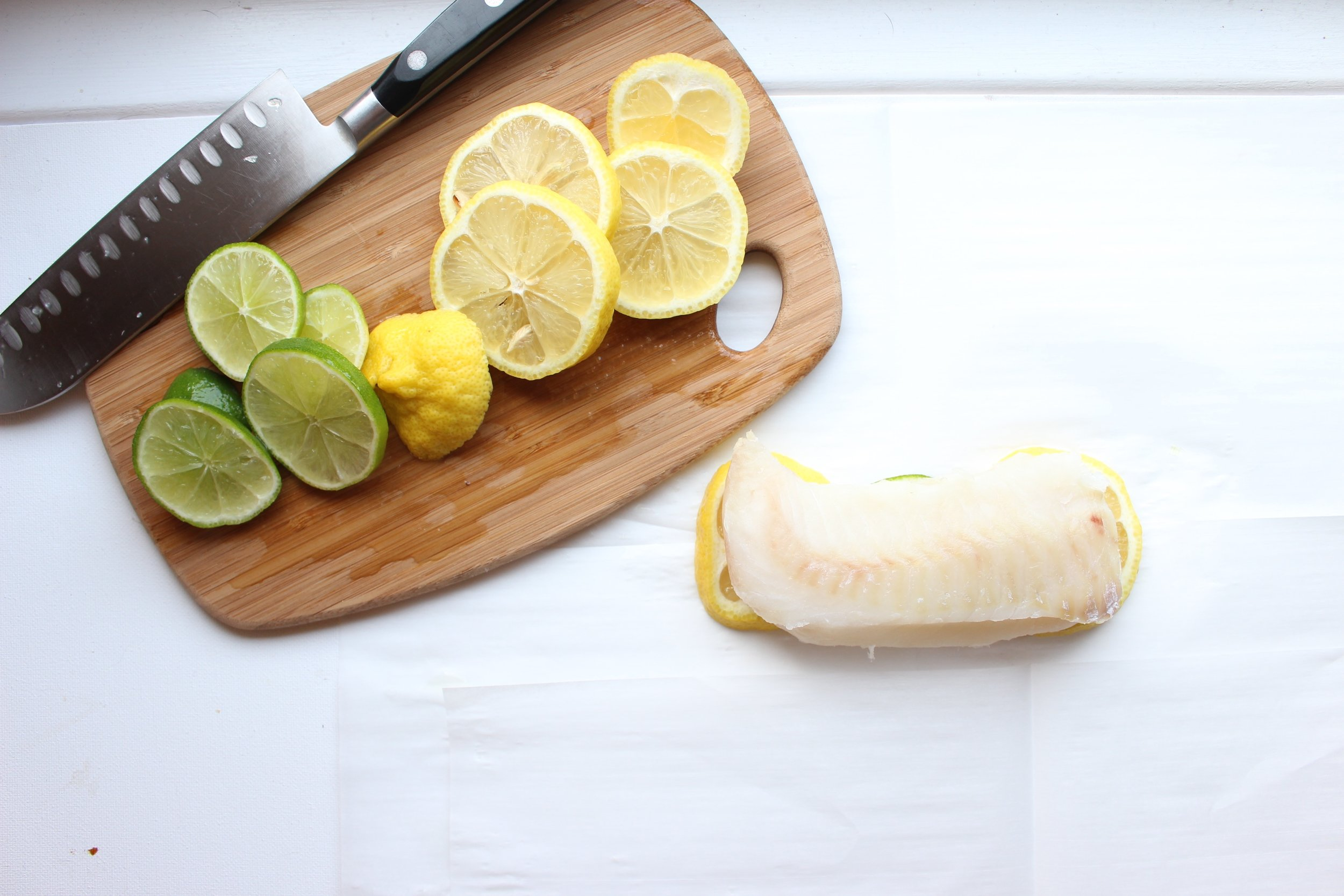 The white fish roasts on a bed of lemons and limes.