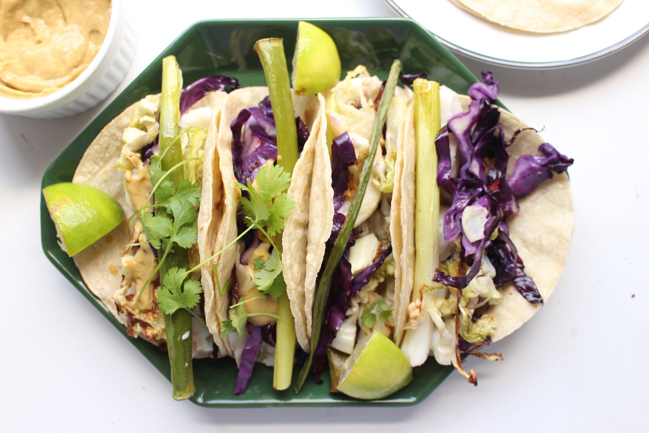 Roasted white fish, cabbage, and scallion tacos that all cook together on a sheet pan.