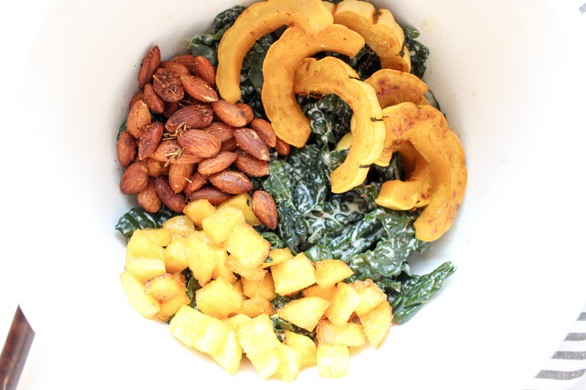 Squash, polenta, and kale Caesar salad | Me & The Moose. Adults and kids alike love this healthy and hearty salad. It combines roasted squash, crispy polenta croutons, roasted spiced almonds, dried cranberries, and a tahini Caesar dressing for a regular weeknight dinner or a special holiday occasion. #meandthemoose #thanksgivingsalad #salad #healthycaesar #delicatasquash #polentacroutons #glutenfree #dairyfree