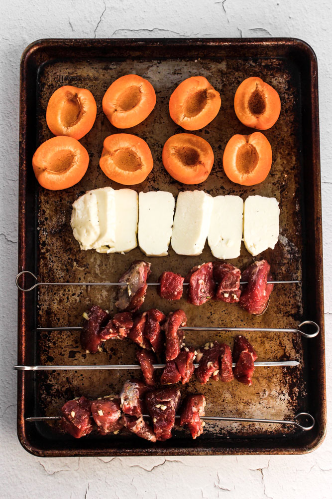 Grilled lamb kebabs with haloumi and apricots | Me & The Moose. Shake up your grill routine with chunks of fatty, savory lamb; melty, salty haloumi cheese; and tart, sweet apricots. #meandthemoose #grilling #lamb #kebabs #haloumi #dinnerrecipes #kebabrecipes #mediterraneandiet #pesto
