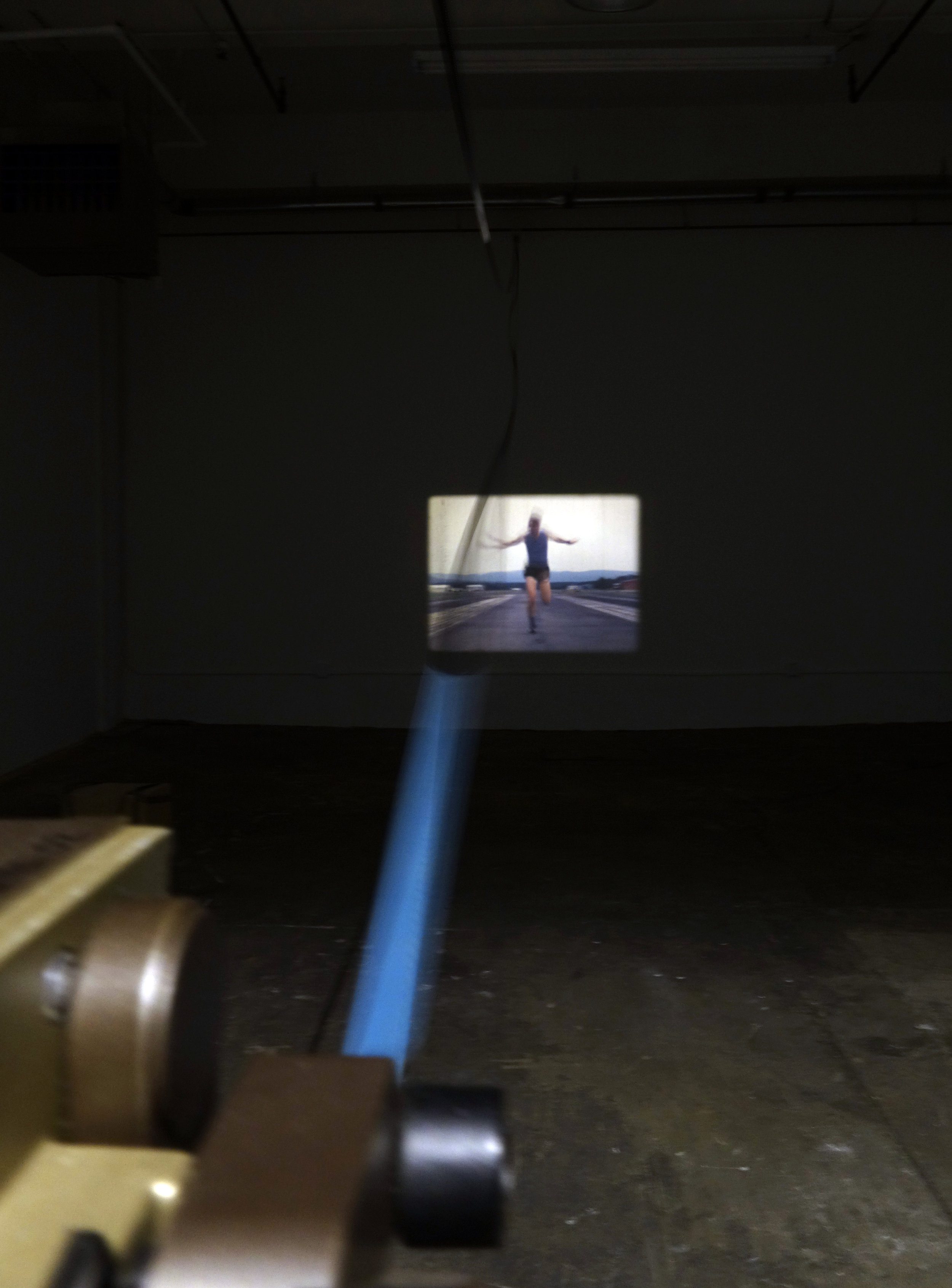 (Installation view 1) Untitled. 16mm film, projector, earth, wood. Approximately 75 x 20 x 5 feet. Duration approximately 4 minutes. 2019.    A 151 foot 16mm video loop of athlete Austen Dalquist running 5000' foot Runway Bravo at Mena Intermountain Airport. The video is a single shot, such that the duration and distance of the run are articulated by the celluloid film in real time.
