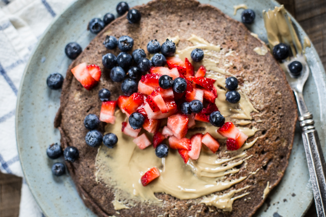 a hearty Giant Buckwheat Pancake topped with berries + sunbutter | edibleperspective.com