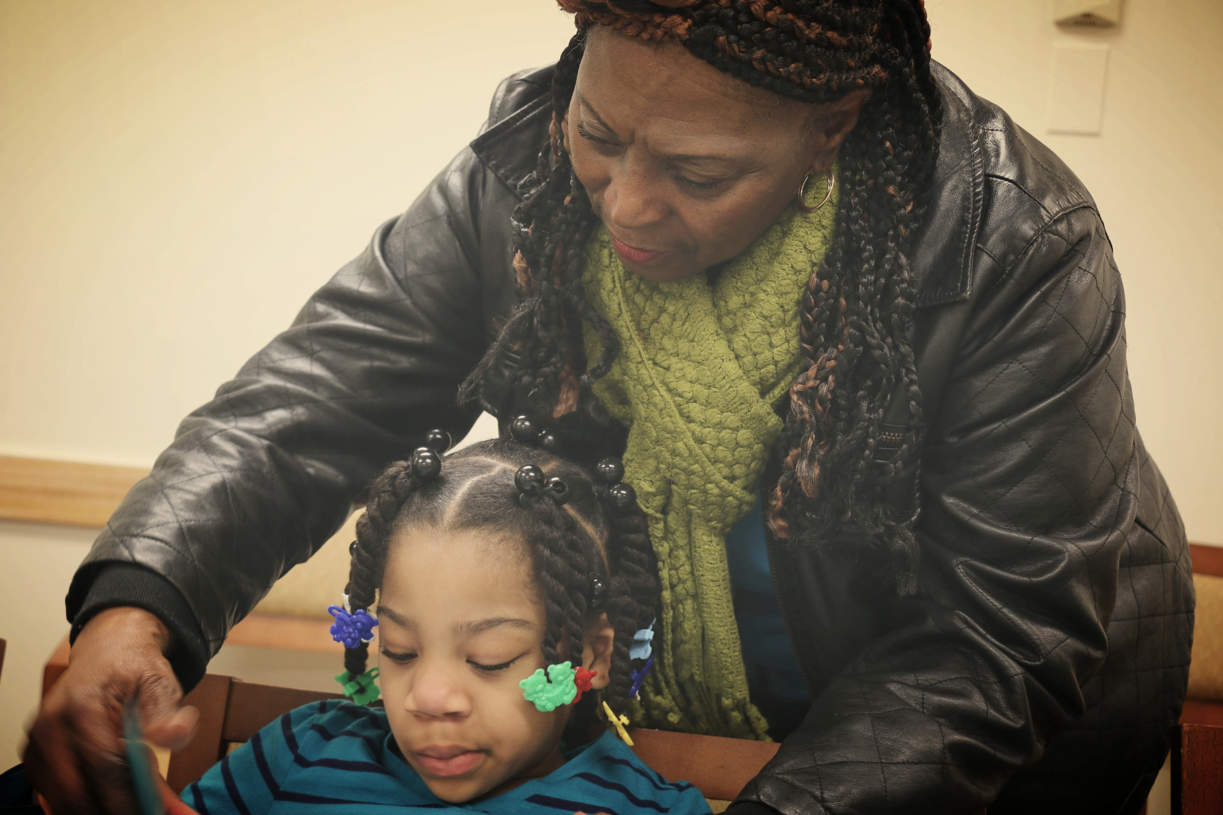 Charlette Purnell, New Jersey Representative, is seen helping a What About YOUth participant with her reading.