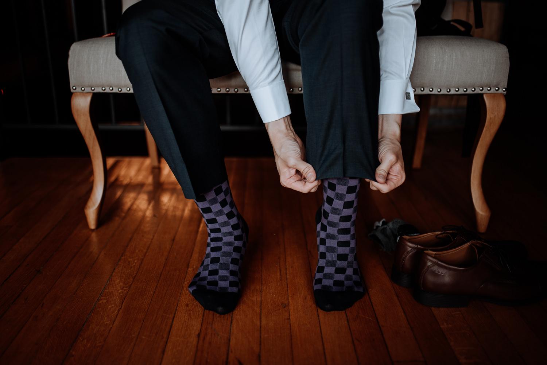 groom puts on purple and black checkerboard socks