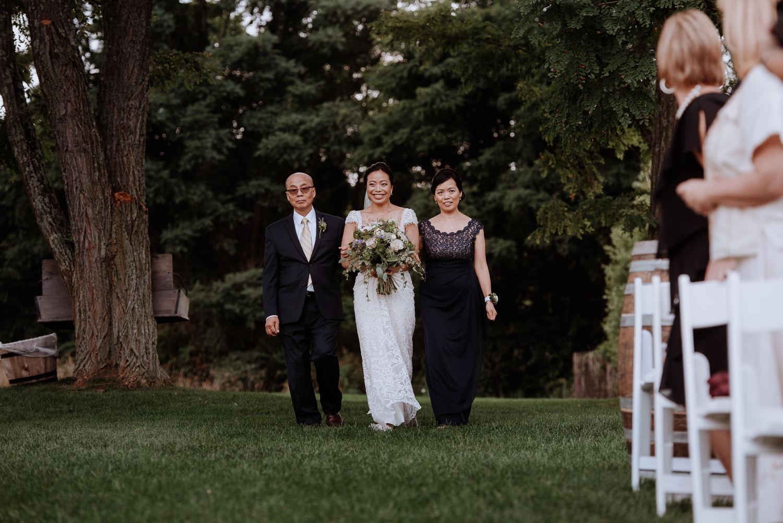Bride walks down aisle at red maple vineyard