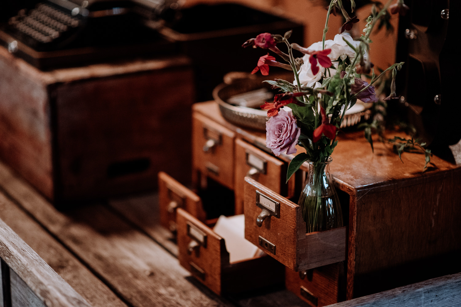 Antique boxes and library card catalog wooden box decorates the card table at this red Maple Vineyard wedding