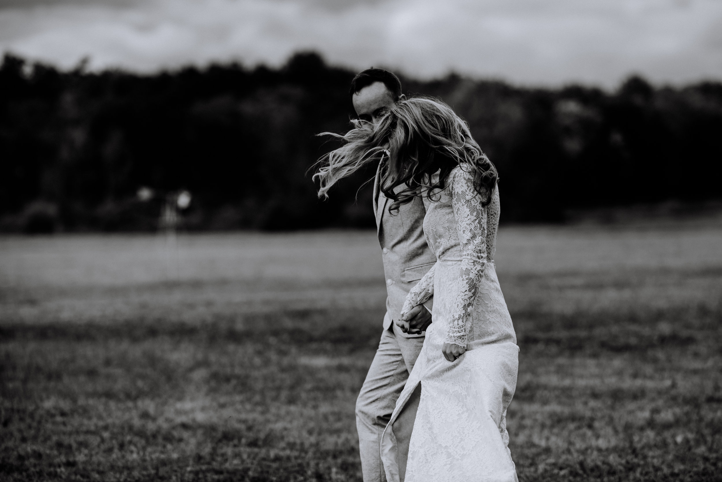black and white candid of the wind in the bride's hair while walking hand in hand with groom
