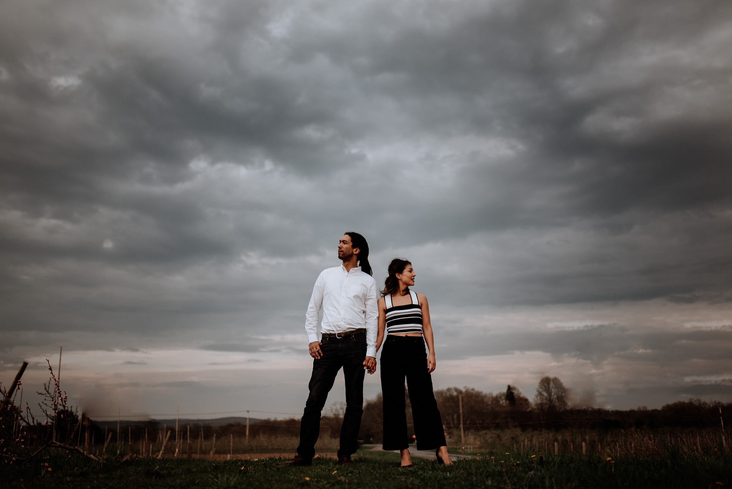 Engaged couple stands on top of a hill in an apple orchard right as the pink apple blossoms were blooming.