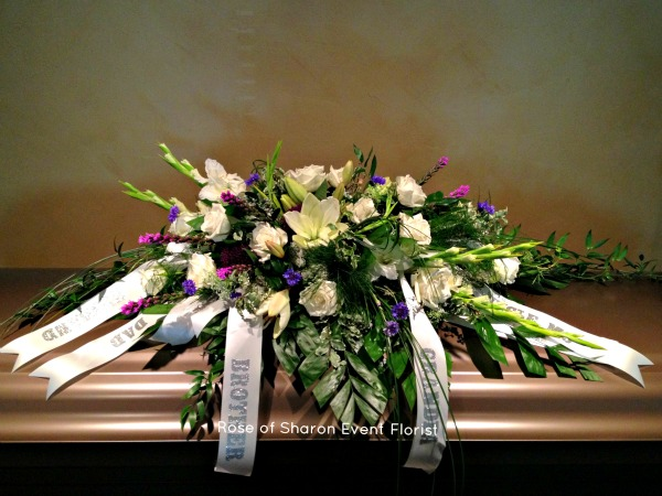 White Lily, blue accent casket spray with tribute ribbons
