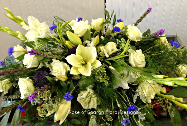 White Lily, blue accent casket spray
