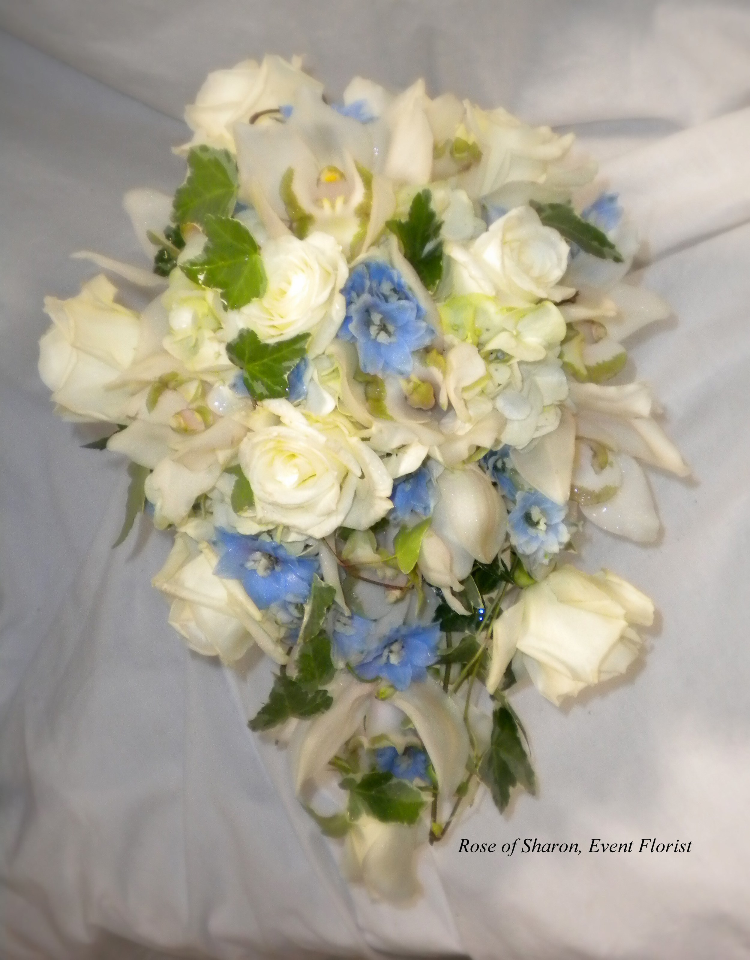 Blue and Cream Teardrop Bouquet with Roses, Orchids and Delphinium. Rose of Sharon Floral Designs