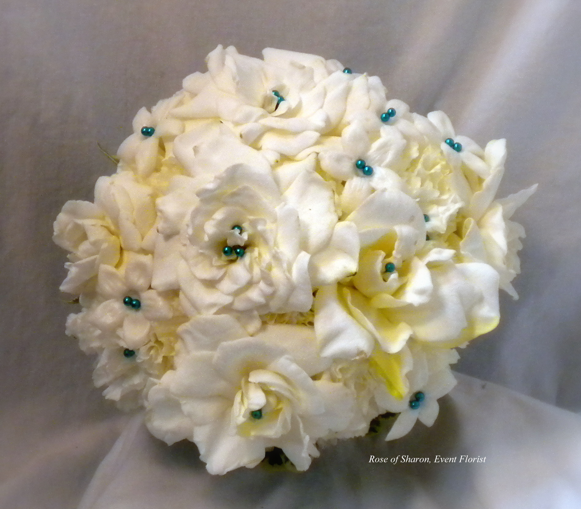 Ivory Hand-Tied Bouquet with Gardenia, Stephanotis, Carnations and Blue Pearl Accents. Rose of Sharon Floral Designs