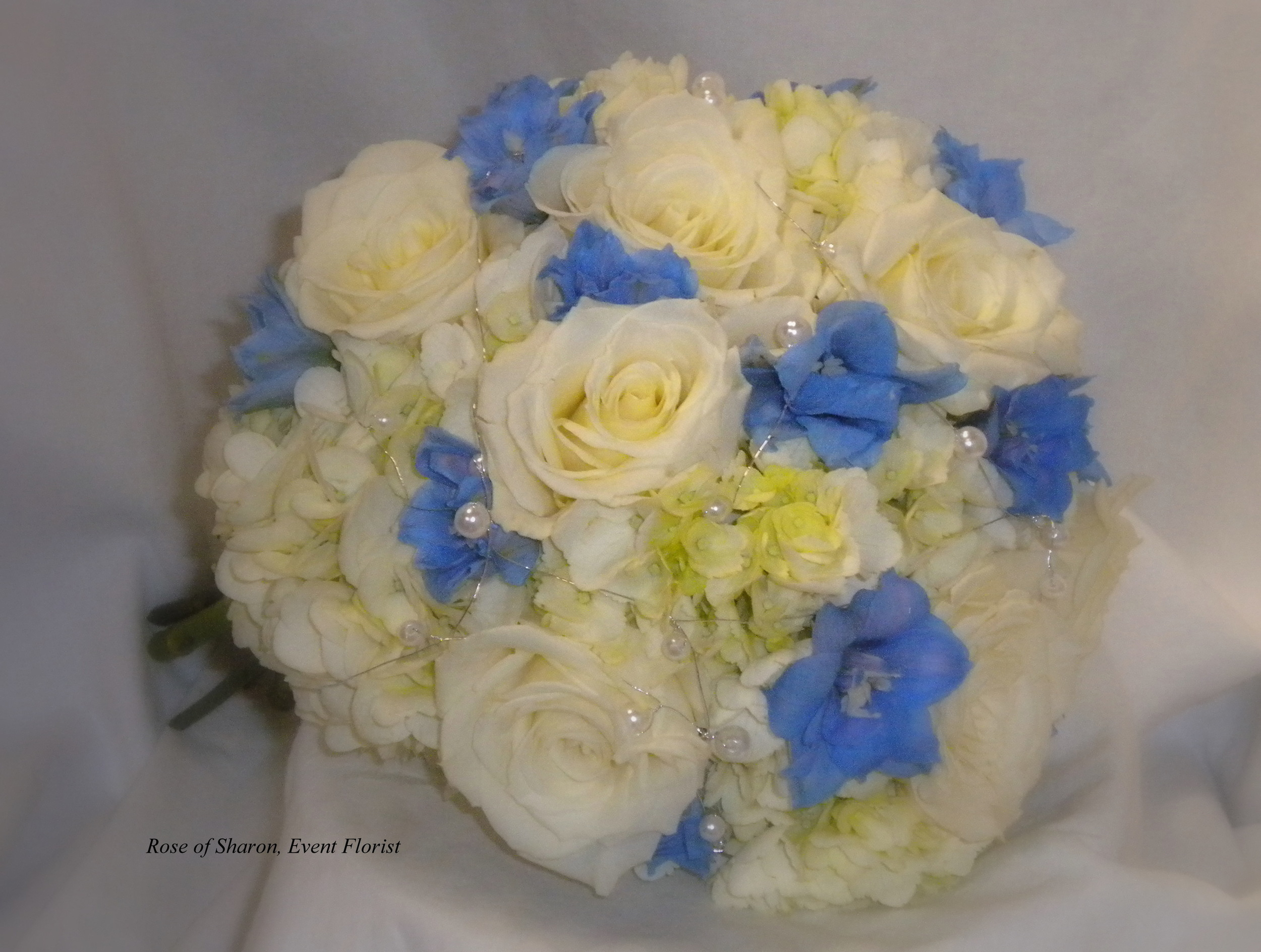 Blue and Ivory Hand-Tied Bouquet with Hydrangeas, Roses, Delphinium and Pearl Accents. Rose of Sharon Floral Designs