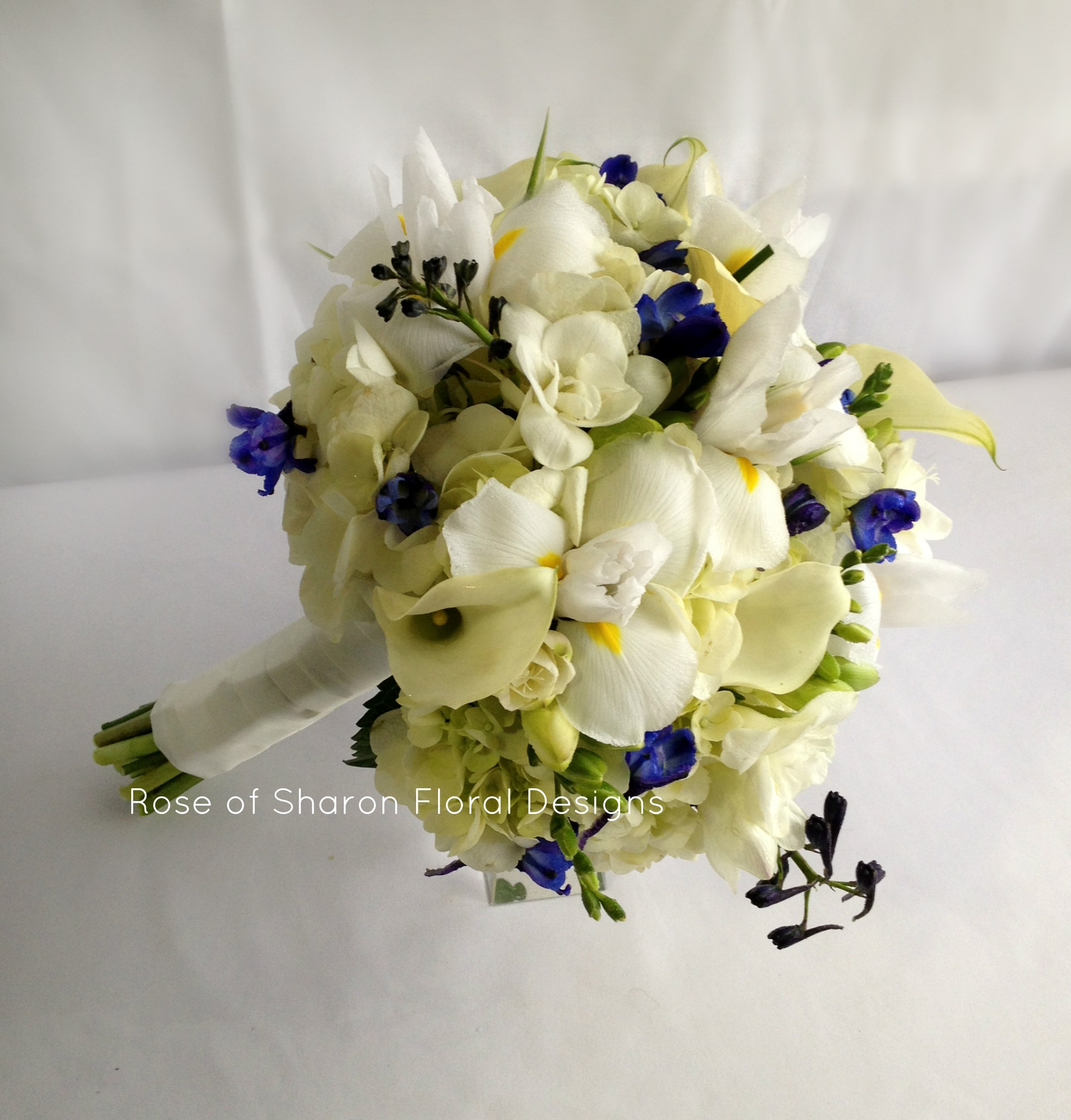 Blue and Ivory Hand-Tied Bouquet with Hydrangeas, Calla Lilies, Irises and Delphinium. Rose of Sharon Floral Designs