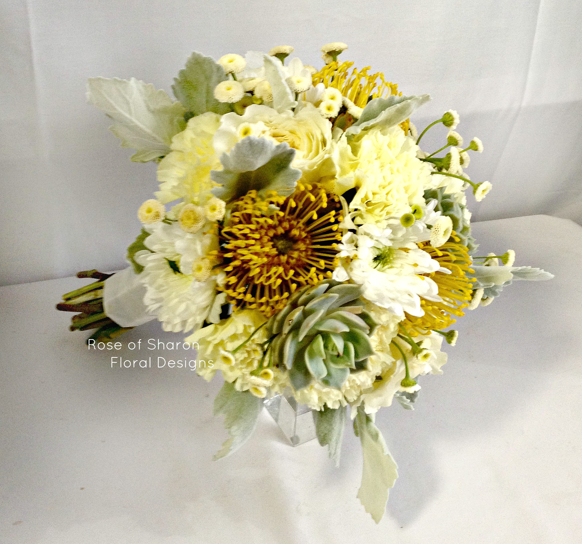 Hand-tied yellow bouquet with pincushion protea & succulents. Rose of Sharon Floral Designs