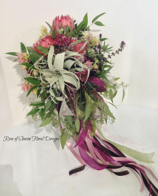 Natural Cascade. Garden bouquet. Pink, plum and green. tillandsia, protea, and eucalyptus. Rose of Sharon Floral Designs.