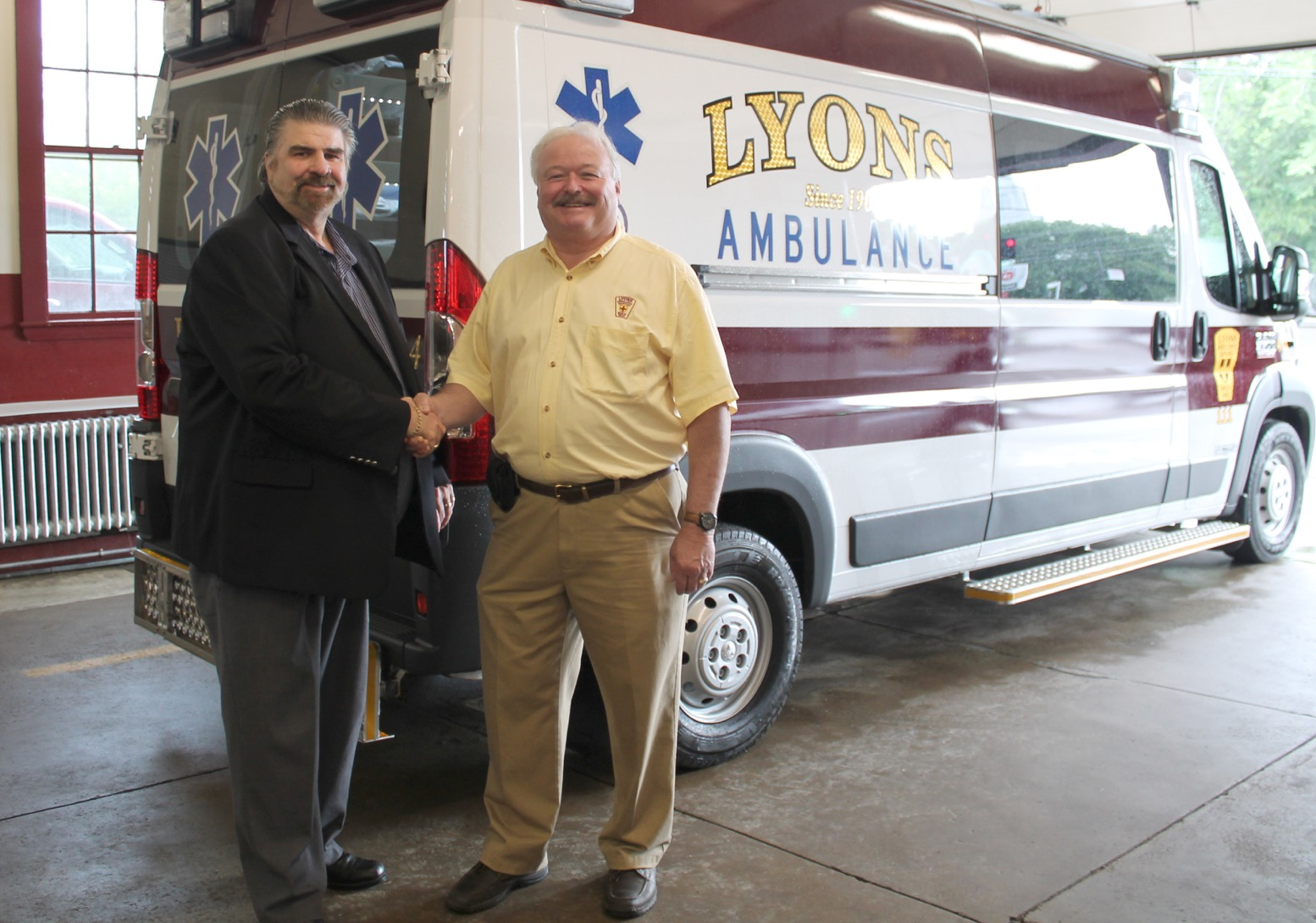 Kevin Lyons, fourth generation at the helm of Lyons Ambulance Service (right) accepts keys to America's first Malley Crossover Ambulance from the manufacturer's President & CEO, Terry Malley.