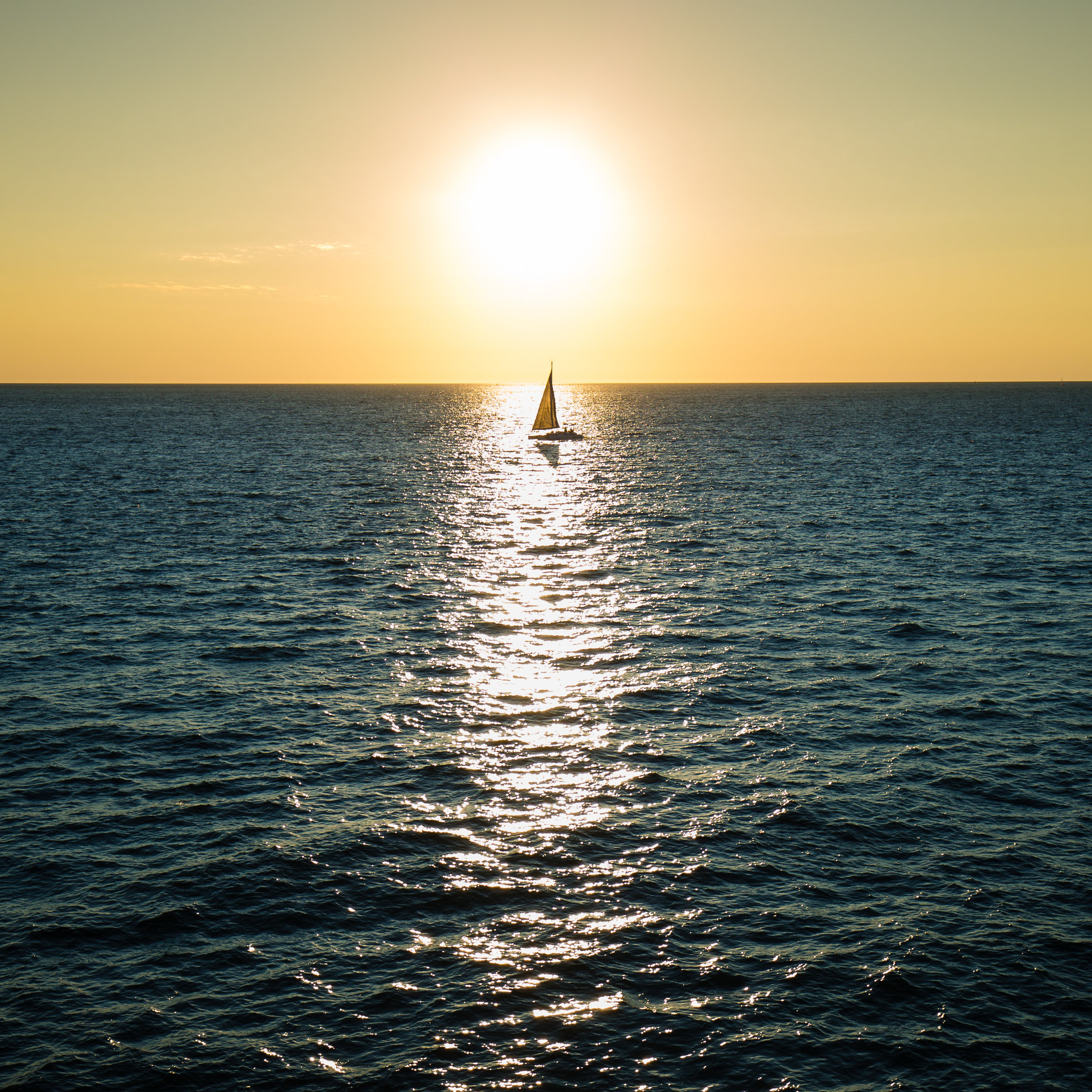 A lone sail boat crosses the early morning sun.