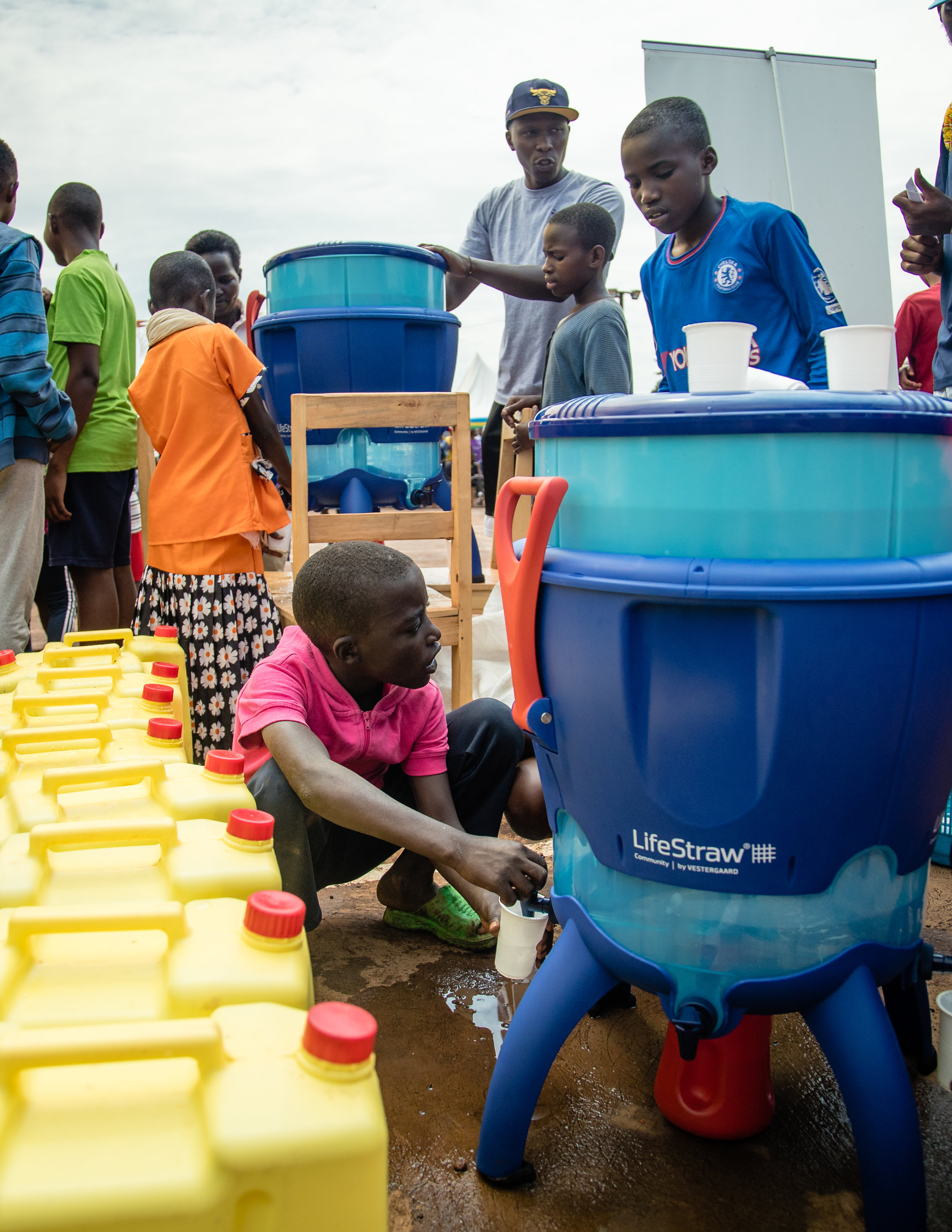 A boy fills up his cup with filtered water located next to the court.
