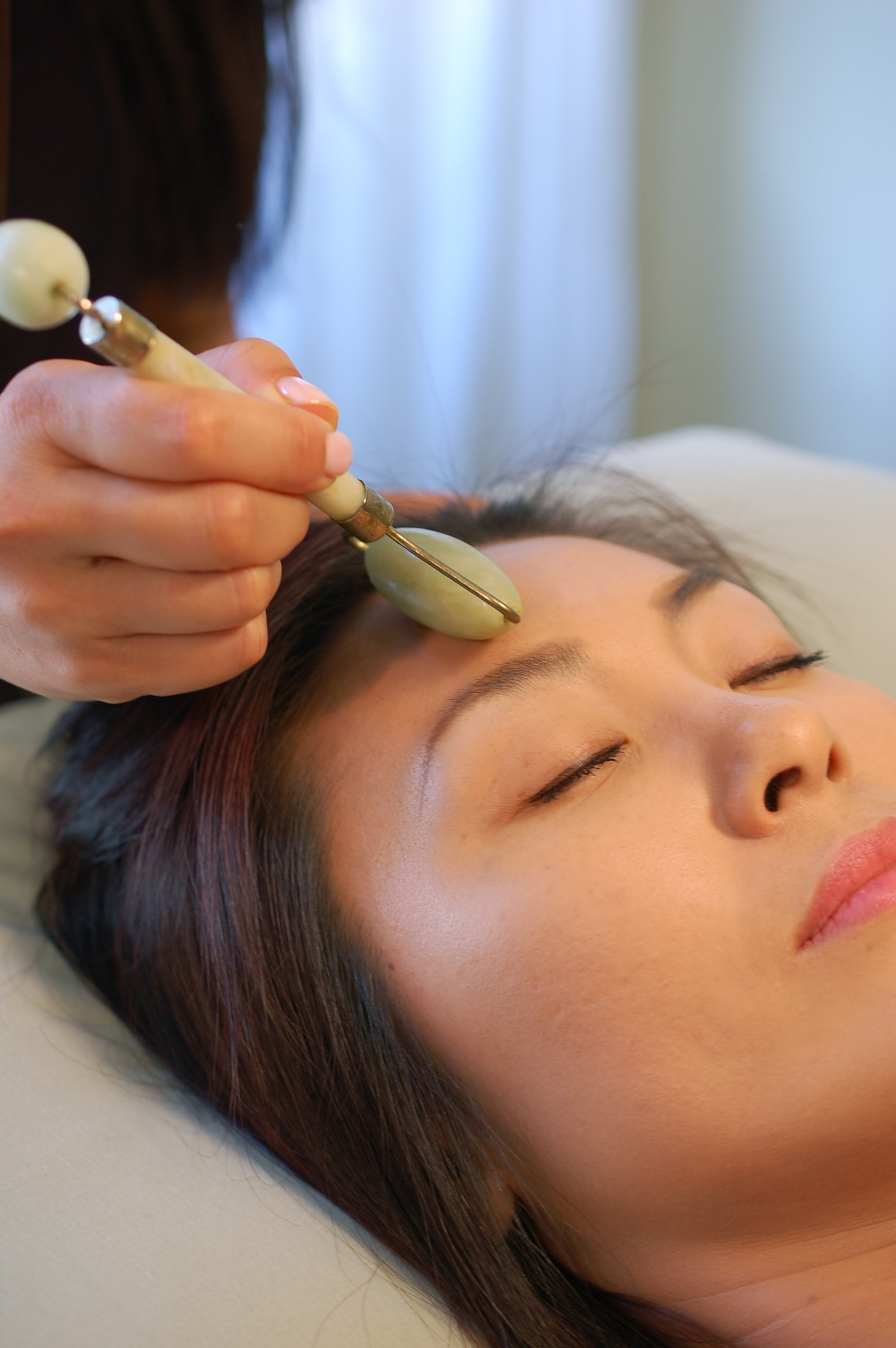 Jade roller to smooth wrinkles and soothe skin