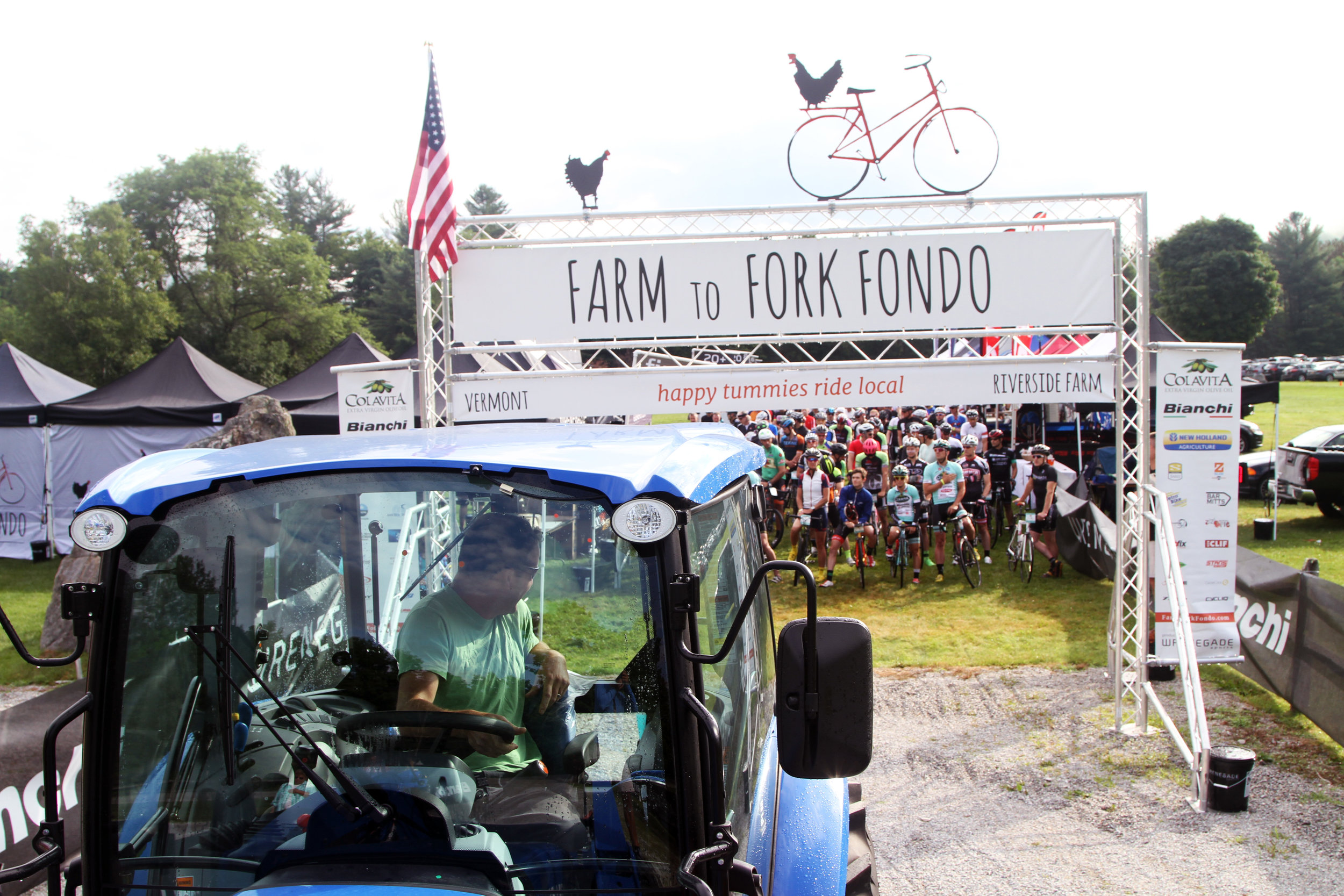 Farm to Fork Fondo – Vermont, a farm to table cycling event series in the Northeast. Local farmer Joe Pimentel leads cyclists in a New Holland tractor
