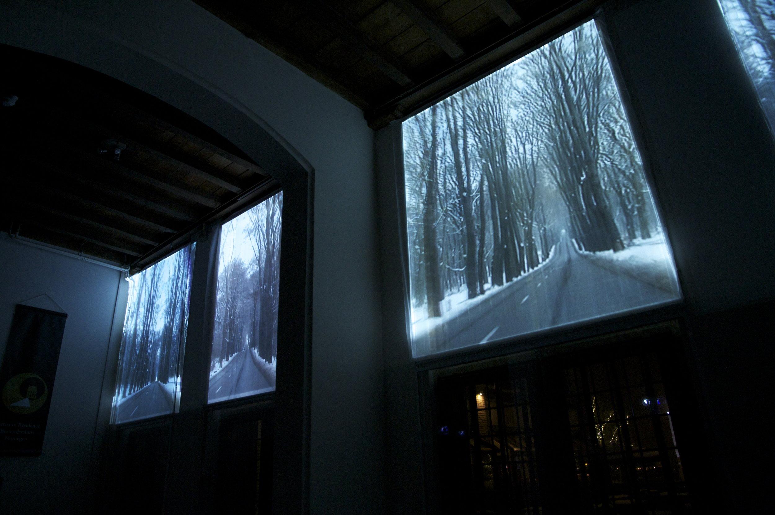 Maries Hendriks - Meanwhile Moments   Mariës Hendriks maakt grafiek en filmwerk met een mysterieuze toonaard. Het filmische kunstwerk dat van binnen naar buiten op de grote glas-in-loodramen van het Besiendershuis geprojecteerd werd, toont een panoramisch beeld; een rit langs een oneindig lange kaarsrechte weg door het bos.