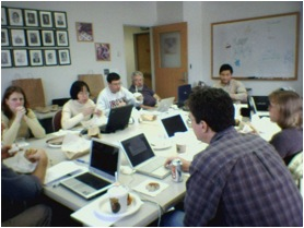 Faculty members working in a group on their laptops.