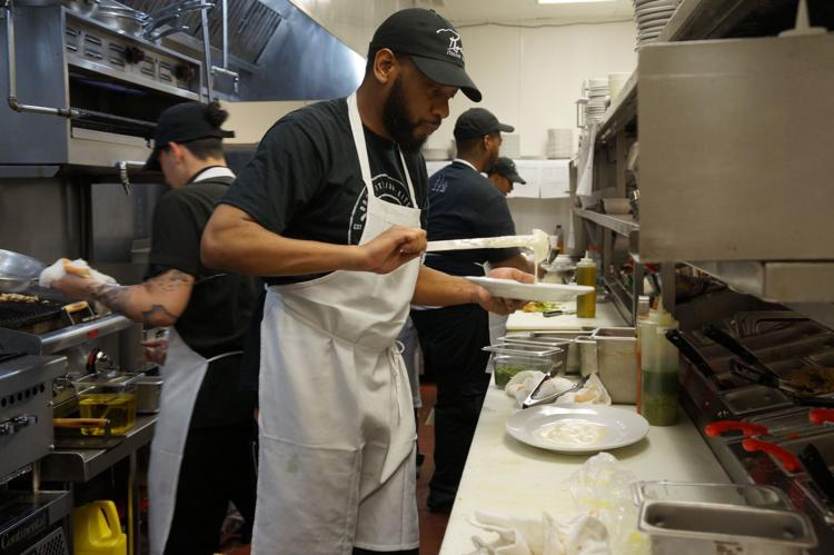 Employees work in the kitchen assembling and plating dishes for customers.