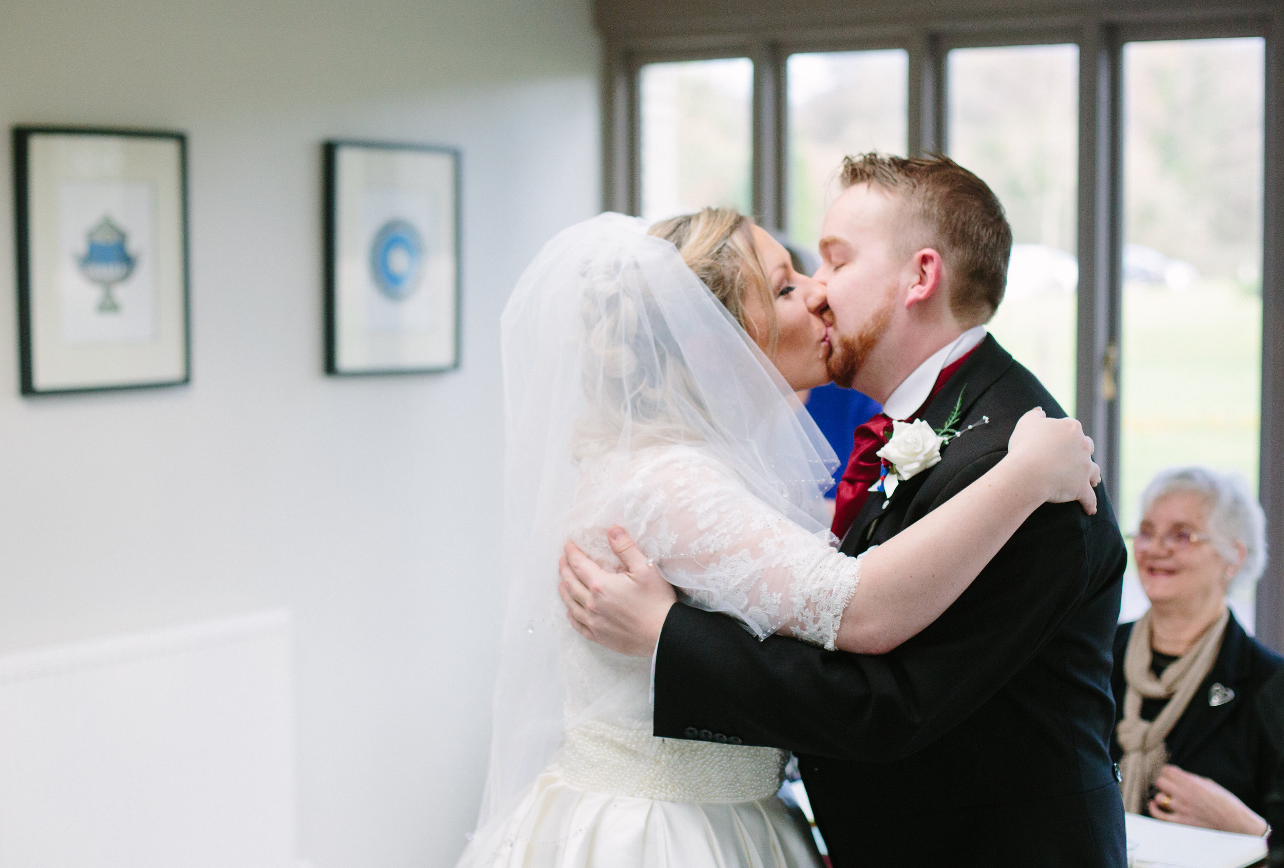 southdowns-manor-sussex-winter-wedding-photography-civil-ceremony-kiss-58
