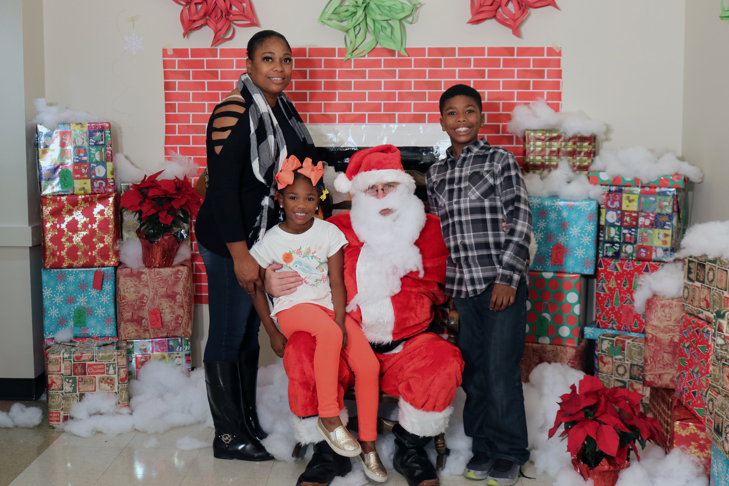 Fortress mom Tasheka and her children Jaidah and Jordan pose with Santa at our Family Christmas Party.