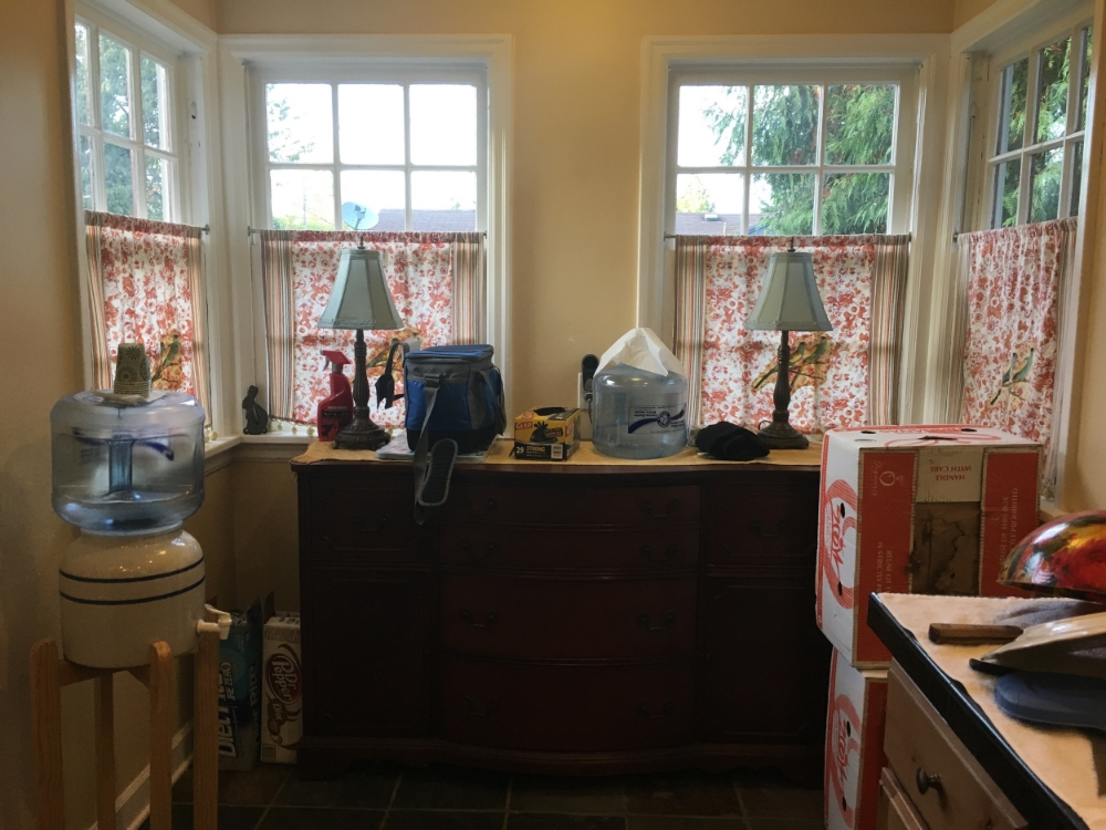 """Before: In the kitchen nook area, the sellers have a large dresser and miscellaneous boxes and other items. It has become a sort of """"catch-all"""" area. It makes the space feel cramped and dark."""
