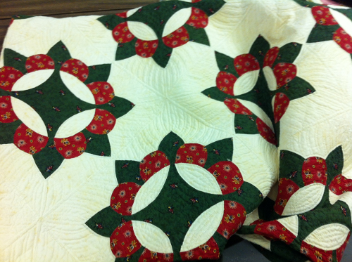 """This quilt is pieced white cotton with green and red calico in a modified """"reel"""" pattern with alternating rounded and pointed petals. Its geometric border alternates green and red diamonds in a zig-zag arrangement. It was made in the 1850s."""