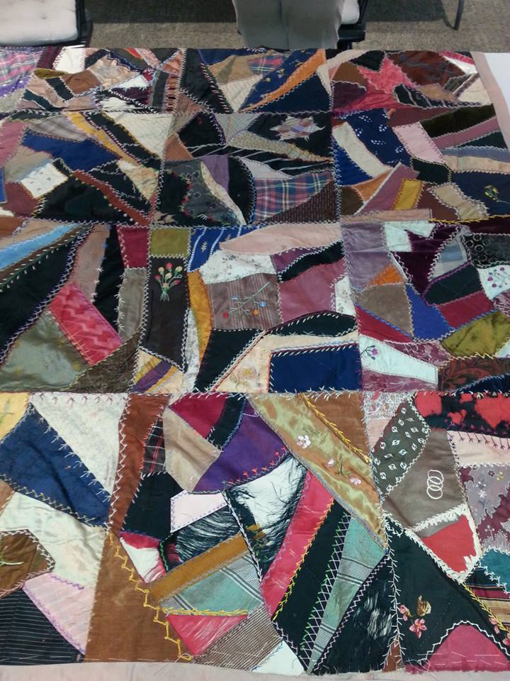 """This Crazy Quilt was made in the mid-1860s for the Wilkinson family. It contains several different types of fabrics with crows feet stitching, an embroidered """"W"""", an anchor, flowers, and """"H S Wilkinson"""" in cursive."""