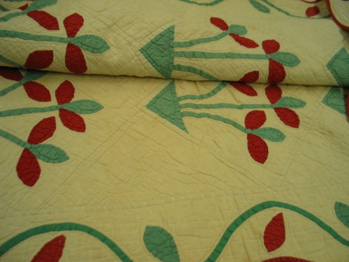 This early 20th-century quilt was hand-sewn with scalloped borders. Its cream-colored background is outlined with red piping. The quilt is filled with green and red flowers.