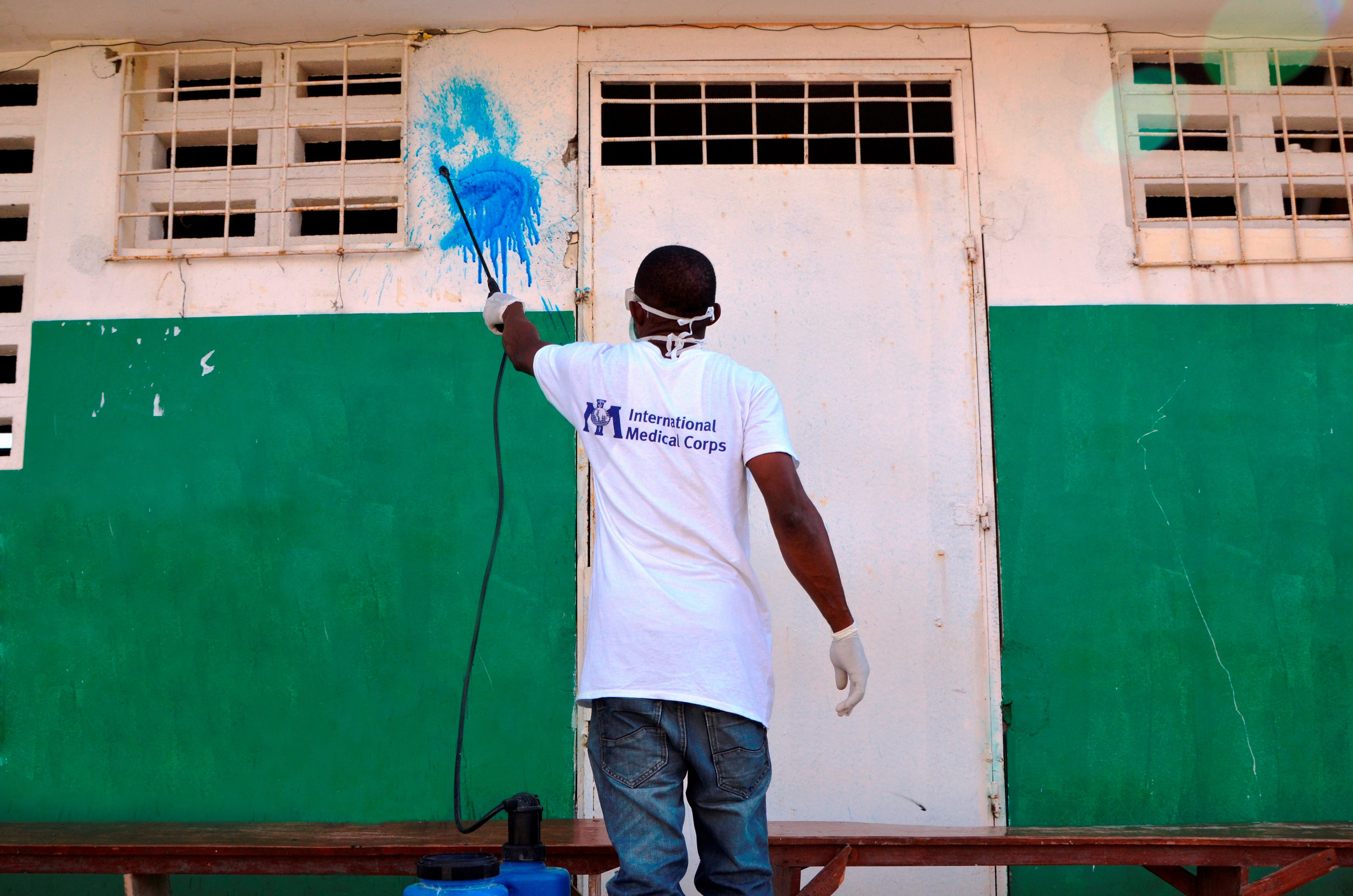 A healthcare worker sprays down a wall with Highlight at a Cholera Treatment Unit in Les Anglais, Haiti. (February 2017). © 2017 International Medical Corps. Photograph by Laura Stana.