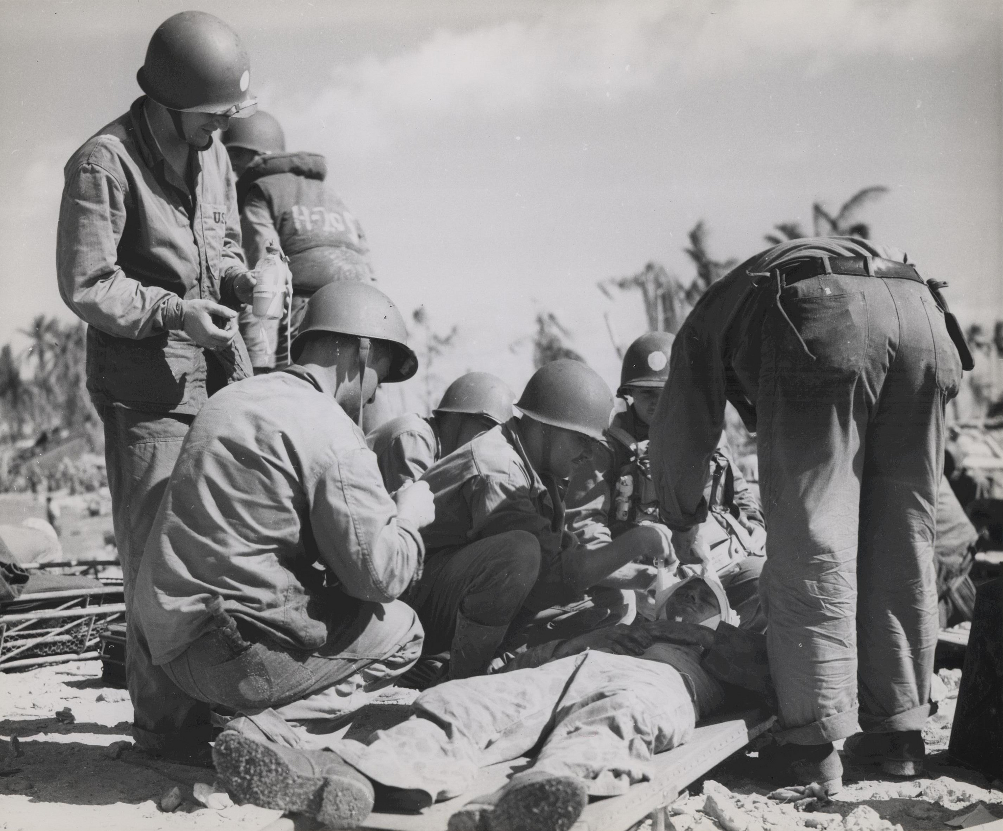 "USMC Archives, ""Navy Corpsman Rendering Aid, Tarawa, November 1943,""  Flickr ,   CC BY 2.0."