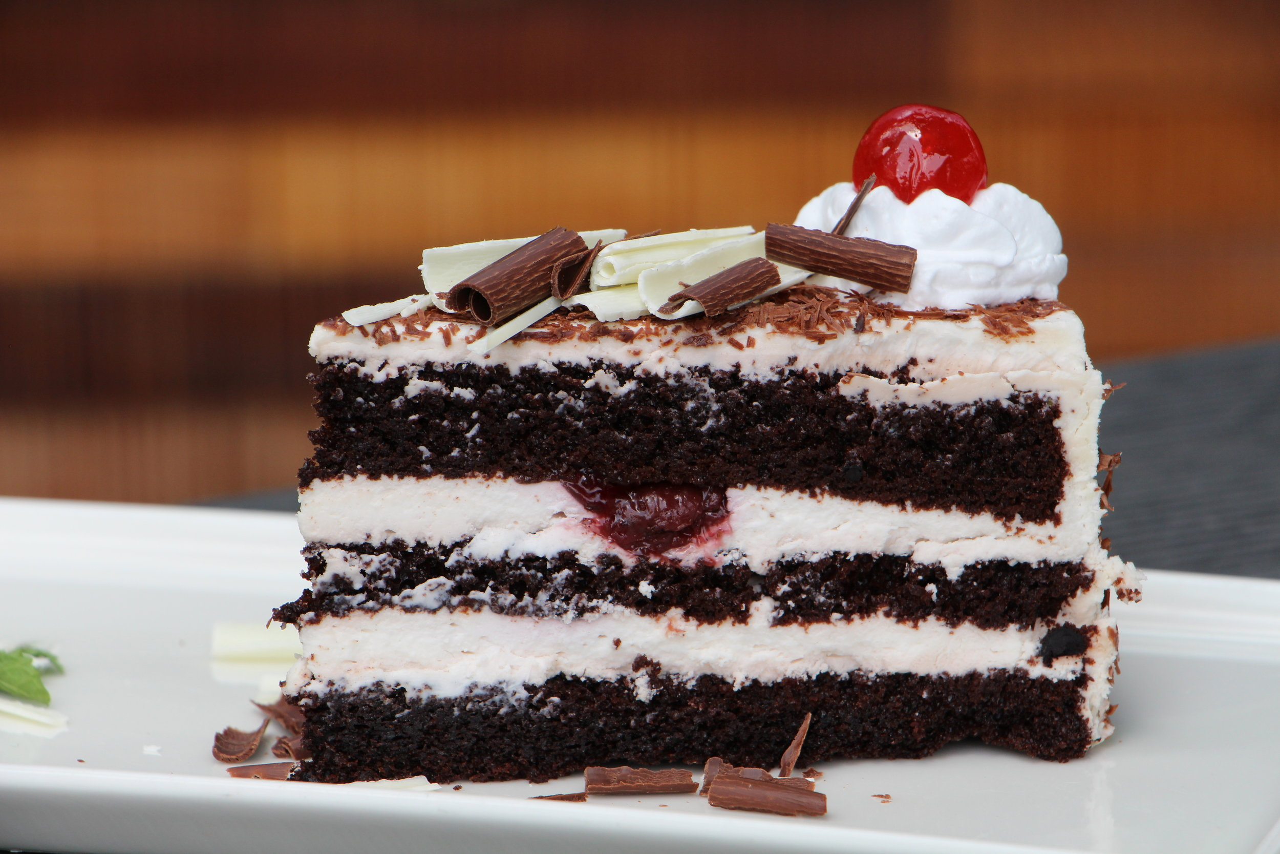 Layers of chocolate cake with fresh whipped cream and maraschino cherries is a classic and never disappoints.
