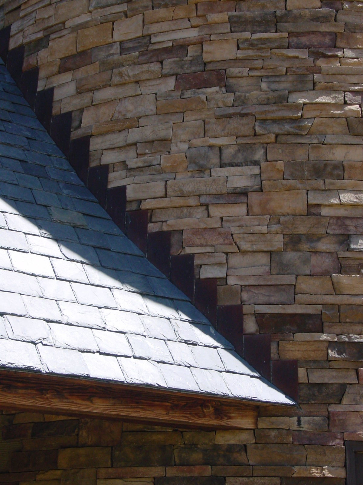 Copper step flashing at the slate roof to stone wall intersection.