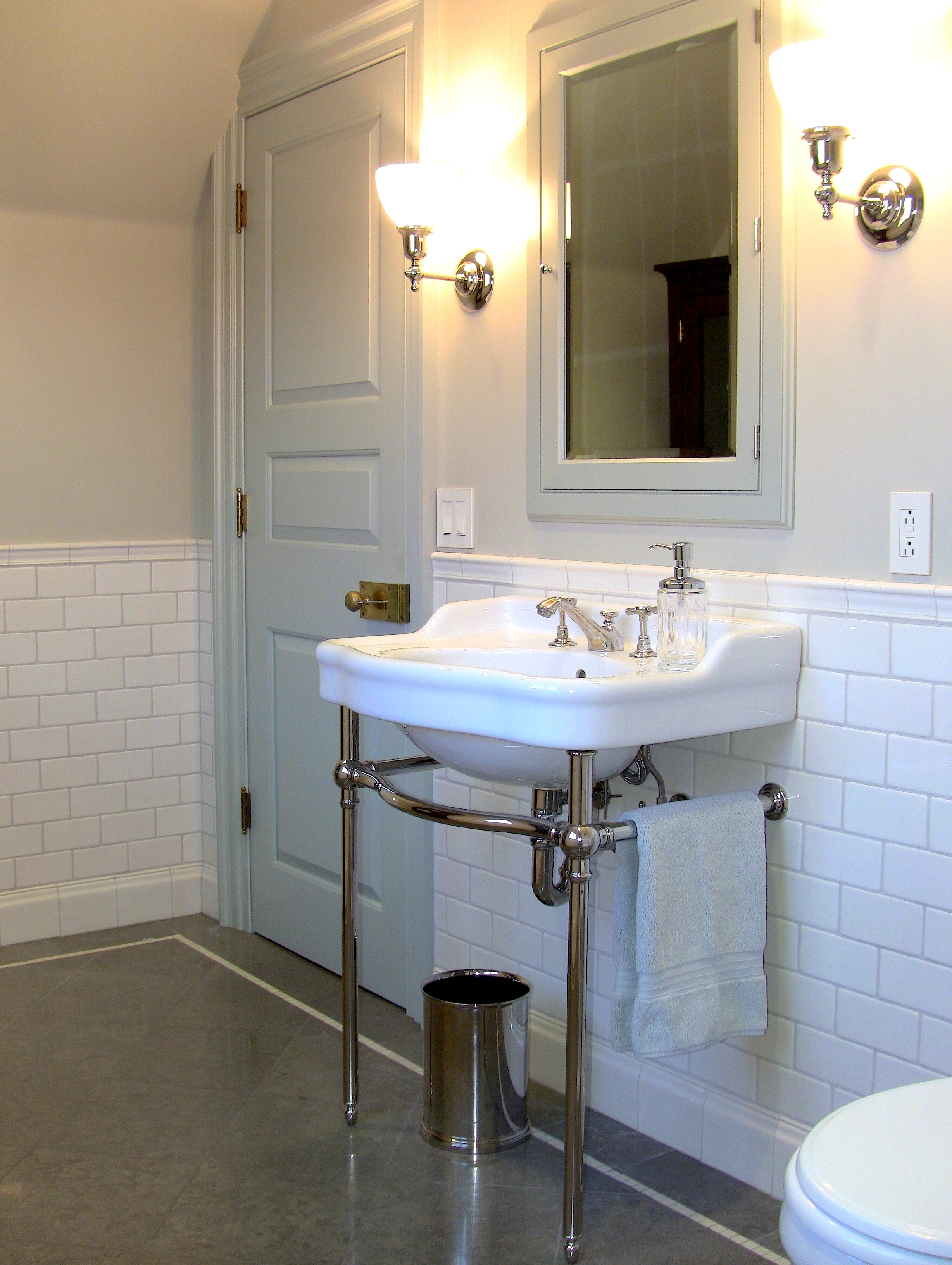 The bathroom for the Blue Bedroom above includes pedestal sink, handmade crackle-glazed tile wainscoting and honed Lagos Azul limestone flooring with a polished marble accent stripe .
