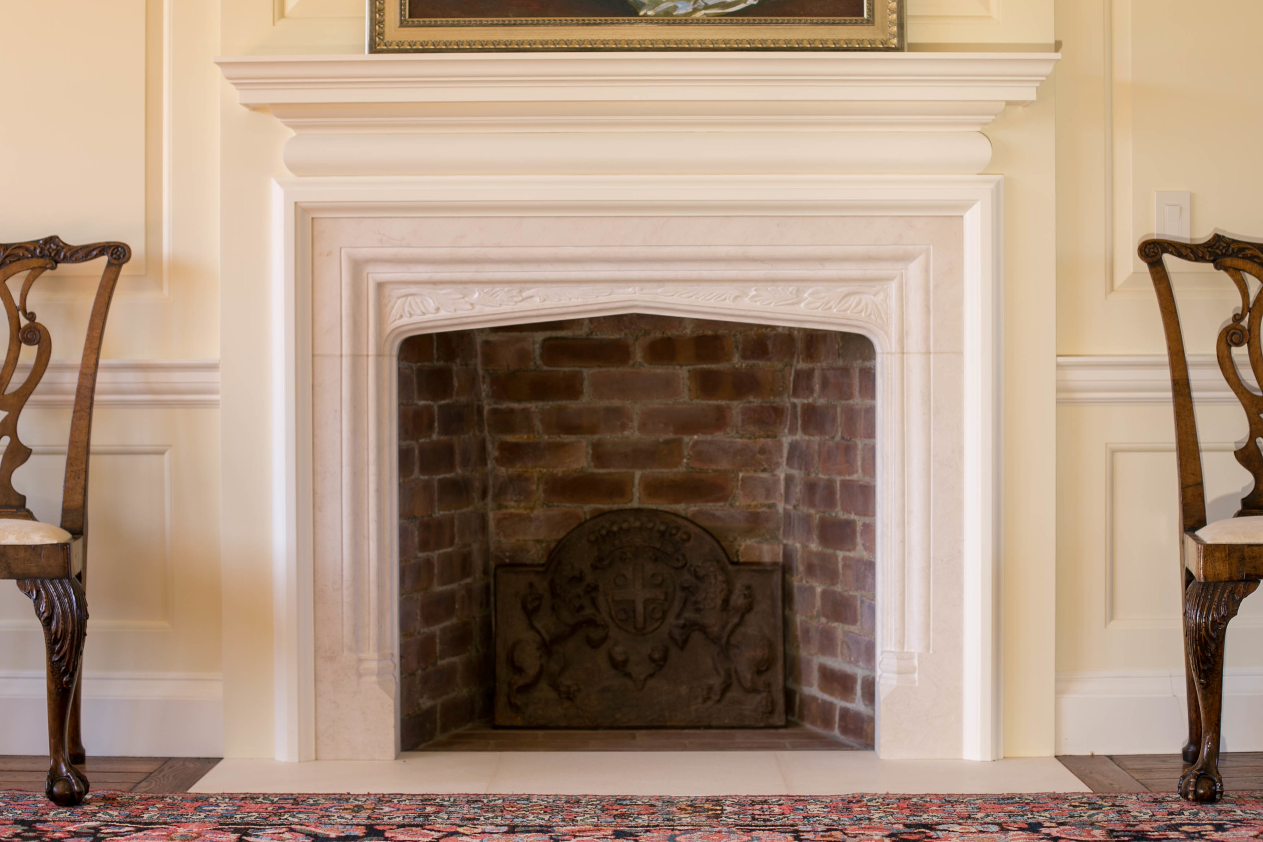A stone mantel in the Tudor style with foliate carving to the spandrels in English Bathstone