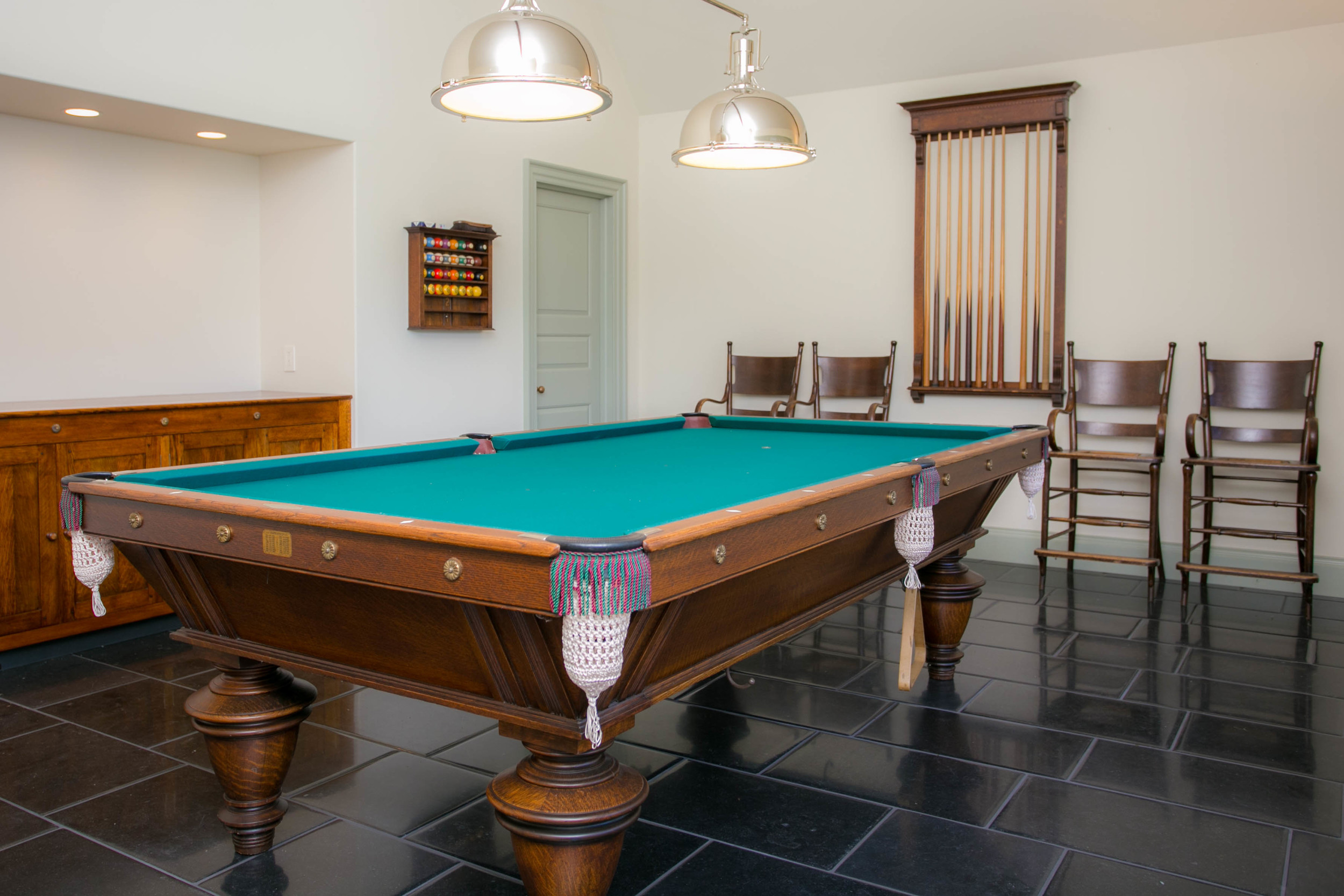 Custom pillow edged Irish blue limestone flooring, quarter-sawn oak cabinetry, bespoke pooltable lights and cathedral ceiling