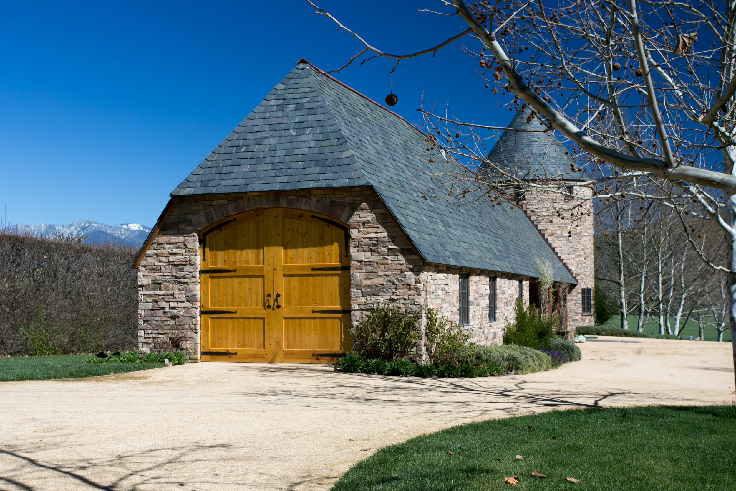 "The stable and tower both have graduated slate and copper roofing with an imported English clay tile ""hogsback"" ridge cap."