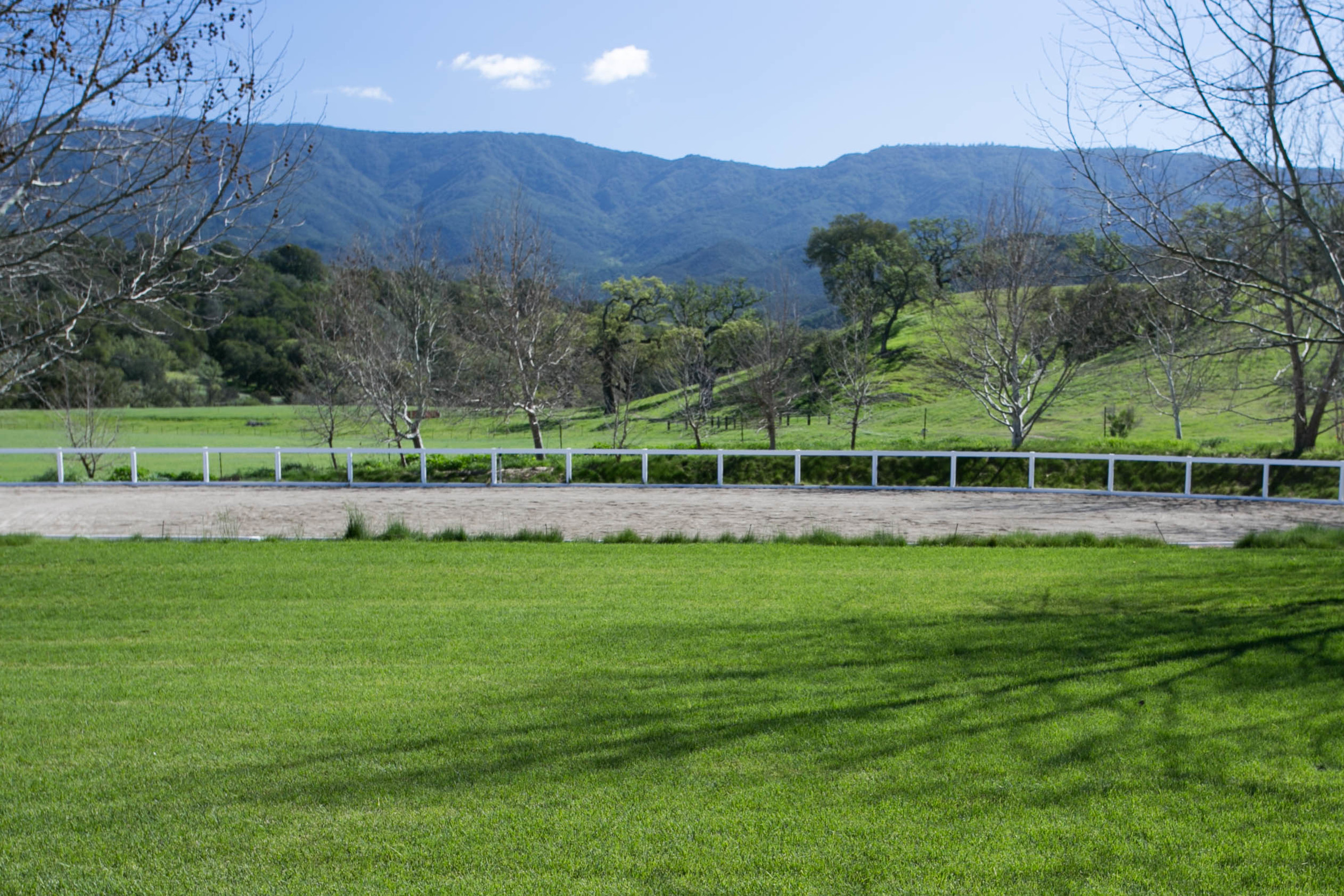 The 110' x 200' Riding Arena is partially sunken into the landscape, which creates a unique vantage point for spectators. The arena is defined by WoodGuard low maintenance rail fencing. This fencing starts with a structurally sound solid wood core treated with a non-toxic organic borate compound to protect against dry rot, termites, and fungus. Finally, it is then coated in an engineered, UV-stabilized plastic blend which requires NO PAINTING...ever. Dust and footing moisture level control is provided by four, recessed and rider safe, 60 gpm Hunter I-90 rotor sprinklers. Application can be automatic or manual at over 120 gallons per minute.