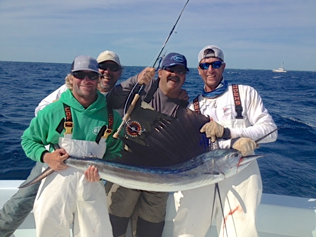 From left,   Chris Eckert, Robert Klein, Tim Klein & Shannon Attales with one of two sails released during the 2015 Sailfly in Islamorada, Florida.