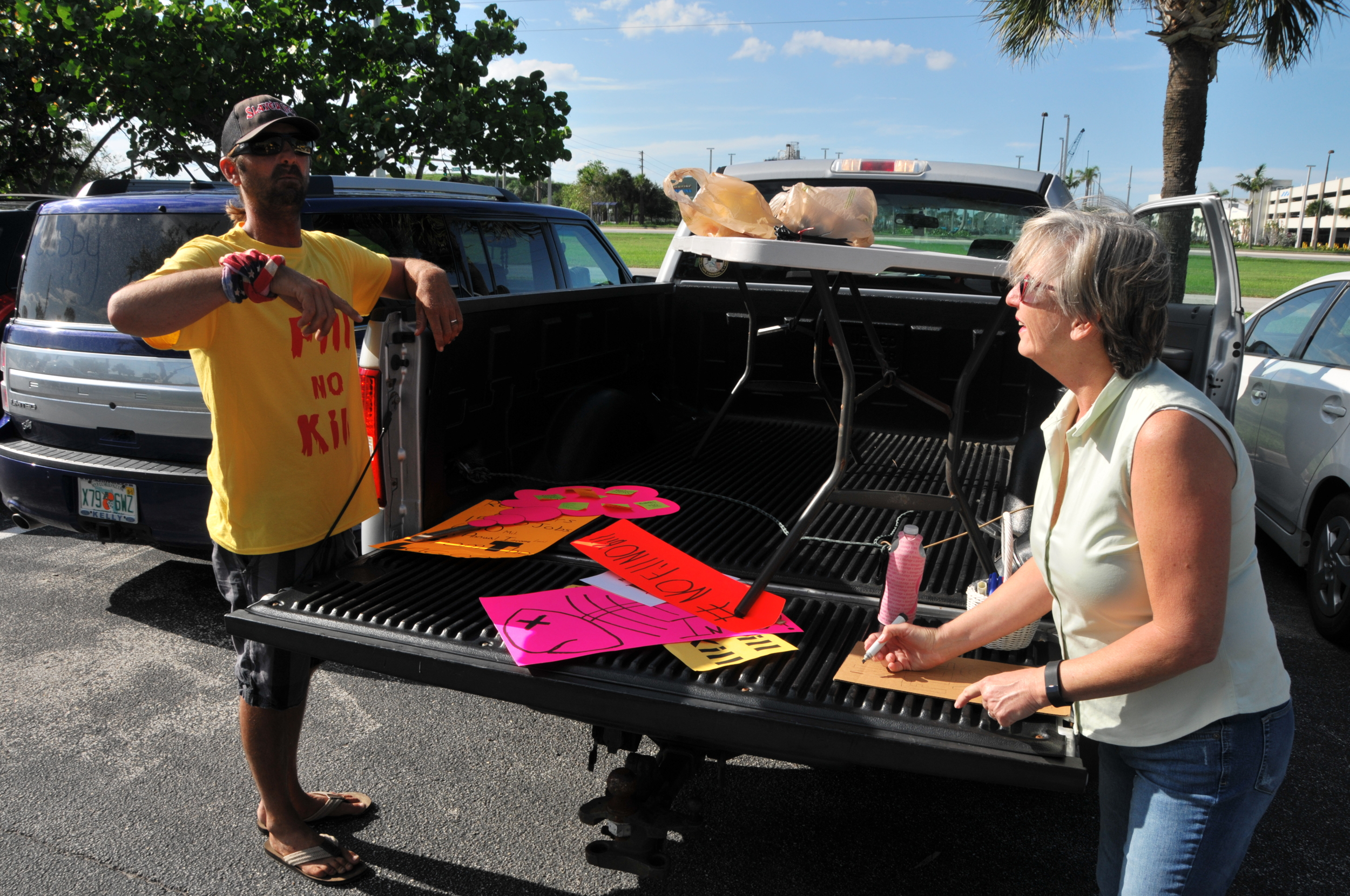 """Alex Gorichky distributes signs for the April 30, 2015 informational meeting held by Port Canaveral. The standing-room-only event — with more than 300 attendees — was the only one held by the CPA, despite assurances by Executive Director John Walsh that meetings would be held """"frequently"""" to keep the public informed on the Canaveral Rail Extension."""