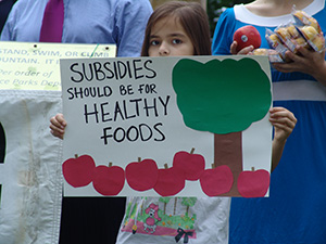 One of the many young protesters at the Aug. 3 press event at Lippitt Park letting farmers market patrons know where she stands when it comes to Twinkies vs. apples. (Frank Carini/ecoRI News)