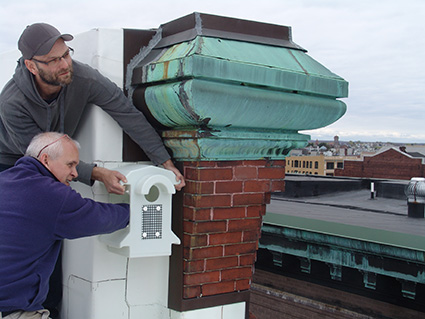 Peter Green, standing, and Peter Gagne install a nest for a kestrel in hopes the tiny raptor will scare away the pigeons nesting on the building across the way. (Frank Carini/ecoRI News)