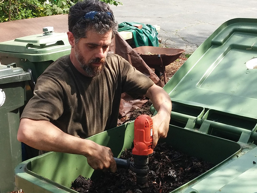 Michael Bradlee, hub manager of the compost operation at Frey Florist on Providence's West Side, uses a powered auger to aerate compost bins. The hub diverts an estimated 1,000 to 1,500 pounds of food scrap from the landfill monthly. (Kevin Proft/ecoRI News)