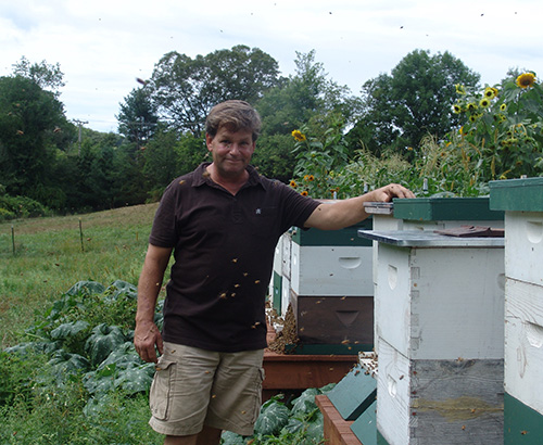 Jon Nelson surrounded by his hives and bees at his friend's farm in North Smithfield, R.I. (Frank Carini/ecoRI News)