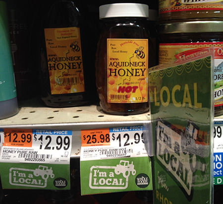 The Whole Foods Market on Waterman Street in Providence clearly markets Aquidneck Honey as a local product. The product's own labels say the honey is 'New England Honey,' 'Pure Raw Local Honey' and 'Pesticide Free.' (Joanna Detz/ecoRI News)